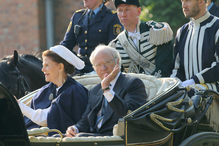 xvi: STOCKHOLM - JUN 06, 2015: The swedish king Carl XVI Gustaf waiving and the queen Silvia Bernadotte sitting in the royal horse wagon on their way to celebrate the swedish national day Editorial
