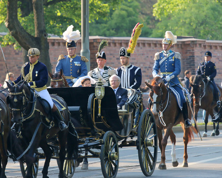 king carl xvi gustaf: STOCKHOLM - JUN 06, 2015: The swedish king Carl XVI Gustaf and the queen Silvia Bernadotte sitting in the royal horse wagon on their way to celebrate the swedish national day