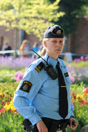 king carl xvi gustaf: STOCKHOLM - JUN 06, 2015: Swedish police woman prepared to protecting the royal family on their way to celebrate the swedish national day Editorial