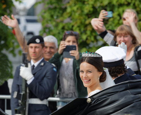 carl: STOCKHOLM - JUN 13, 2015: The swedish Prince Carl-Philip Bernadotte and his wife Princess Sofia Hellqvist a few minutes after the royal wedding smiling and waiving to the audience