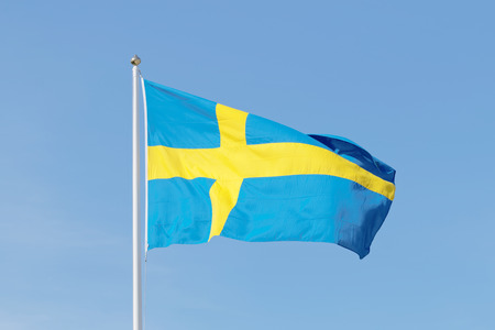 Swedish flag outside the Royal castle, blue and a yellow cross and background of blue sky photo