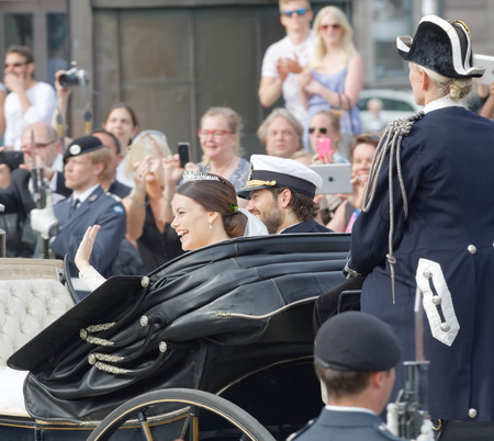 royal wedding: STOCKHOLM - JUN 13, 2015: The swedish Prince Carl-Philip Bernadotte and his wife Princess Sofia Hellqvist a few minutes after the royal wedding smiling and waiving to the audience in Stockholm, June 13 2015 Editorial