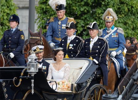 royal wedding: STOCKHOLM - JUN 13, 2015: The royal coach carrying the swedish Prince Carl-Philip Bernadotte and his wife Princess Sofia Hellqvist a few minutes after the royal wedding in Stockholm, June 13 2015 Editorial