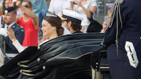 royal wedding: STOCKHOLM - JUN 13, 2015: Rear view of the swedish Prince Carl-Philip Bernadotte and his wife Princess Sofia Hellqvist a few minutes after the royal wedding smiling and waiving to the audience in Stockholm, June 13 2015 Editorial