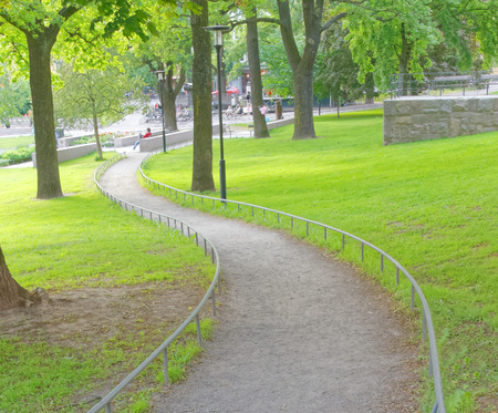 sweden resting: STOCKHOLM - JUN 13, 2015: Meander path in the public park Vasaparken with green trees, grass and distant people relaxing, June 13, 2015 in Stockholm, Sweden