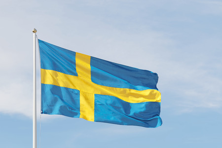 Swedish flag outside the Royal castle, blue and a yellow cross and background of blue sky and white clouds photo