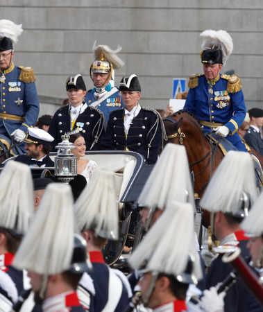royal wedding: STOCKHOLM - JUN 13, 2015: The royal coach carrying the swedish Prince Carl-Philip Bernadotte and his wife Princess Sofia Hellqvist a few minutes after the royal wedding, smiling to the audience in Stockholm, June 13 2015