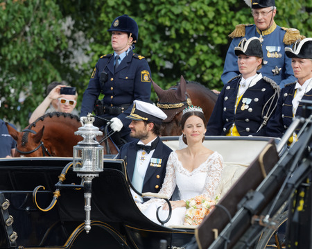 royal wedding: STOCKHOLM - JUN 13, 2015: The royal coach carrying the swedish Prince Carl-Philip Bernadotte and his wife Princess Sofia Hellqvist a few minutes after the royal wedding in Stockholm, June 13, 2015