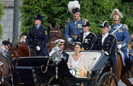 royal wedding: STOCKHOLM - JUN 13, 2015: The royal coach carrying the swedish Prince Carl-Philip Bernadotte and his wife Princess Sofia Hellqvist a few minutes after the royal wedding, smiling and waiving to the audience in Stockholm, June 13 2015