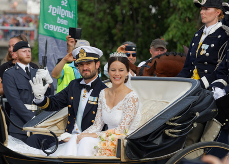 royal wedding: STOCKHOLM - JUN 13, 2015: Fron view of the swedish Prince Carl-Philip Bernadotte and his wife Princess Sofia Hellqvist a few minutes after the royal wedding, smiling and waiving to the audience in Stockholm, June 13 2015 Editorial