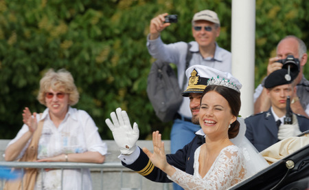 royal wedding: STOCKHOLM - JUN 13, 2015: The swedish Prince Carl-Philip Bernadotte and his wife Princess Sofia Hellqvist a few minutes after the royal wedding, smiling and waiving to the audience in Stockholm, June 13 2015
