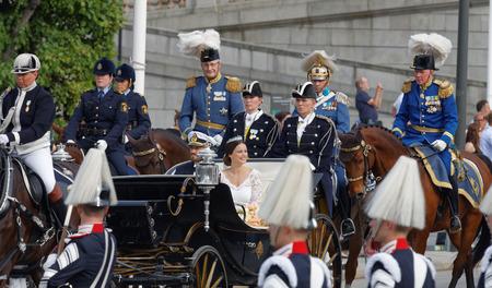 royal wedding: STOCKHOLM - JUN 13, 2015: The royal coach carrying the swedish Prince Carl-Philip Bernadotte and his wife Princess Sofia Hellqvist a few minutes after the royal wedding in Stockholm, June 13 2015 Editorial