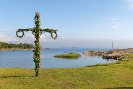 midsummer pole: Maypole used to celebrate the midsummer, the arrival of the summer. The swedish archipelago in the background Stock Photo