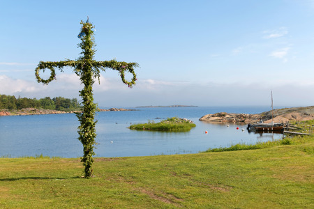 maypole: Maypole used to celebrate the midsummer, the arrival of the summer. The swedish archipelago in the background Stock Photo