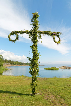 Maypole used to celebrate the midsummer, the arrival of the summer. The swedish archipelago in the background Stock Photo
