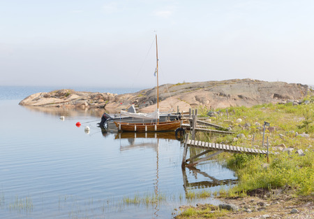 floaters: Wooden sailboat and small bridges in the archipelago a summer morning with calm water