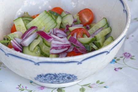 Sallad consisting of tomato, red onion and cucumber in a white and blue bowl standing on a textured cloth Stock Photo