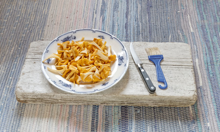 mycology: Cleanded group of chantarelles on a on a plate standing on a gray plank