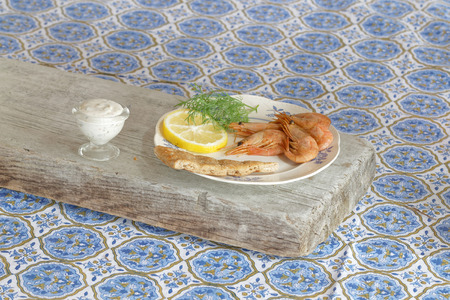 side plate: Swedish delicacy consisting of a plate of smoked shrimp, lemon, bread, aioli and dill on a table with a blue textured cloth, side view