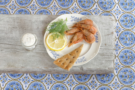 consisting: Swedish delicacy consisting of a plate of smoked shrimp, lemon, bread, aioli and dill on a table with a blue textured cloth
