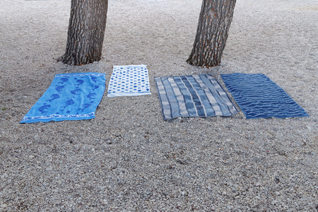 differnt: Four blue blankets with differnt textures on the beach below the pine trees. Used to book the best places on the beach Stock Photo
