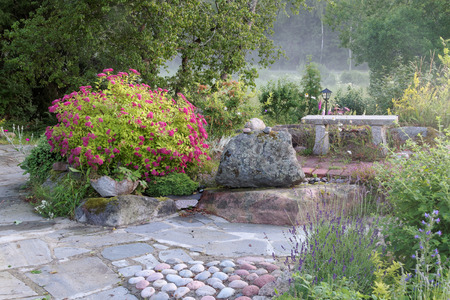plats: Beautiful garden with pink and blue plats, a bench of stone and an alley made of slate stone
