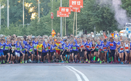 12 year old: STOCKHOLM, SWEDEN - AUG 15, 2015: Group of 12 year old girls and boys starting  the running event Midnattsloppet, August 15, 2015 in Stockholm, Sweden