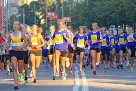 13 year old: STOCKHOLM, SWEDEN - AUG 15, 2015: Group of 13 year old girls and boys running in the running event Midnattsloppet, August 15, 2015 in Stockholm, Sweden