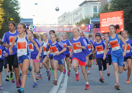 12 year old: STOCKHOLM, SWEDEN - AUG 15, 2015: Group of 12 year old girls in blue dresses running in the running event Midnattsloppet, August 15, 2015 in Stockholm, Sweden