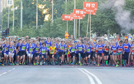 12 year old: STOCKHOLM, SWEDEN - AUG 15, 2015: Group of 12 year old girls and boys running in the running event Midnattsloppet, August 15, 2015 in Stockholm, Sweden