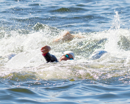 woman squirt: STOCKHOLM - AUG 22, 2015: Closeup of female crawler wearing swim glasses in the water in the Womens ITU World Triathlon series event August 22, 2015 in Stockholm, Sweden Editorial