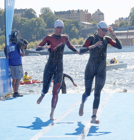 woman squirt: STOCKHOLM - AUG 22, 2015: Two female swimmer climbing up from the water in the Womens ITU World Triathlon series event August 22, 2015 in Stockholm, Sweden