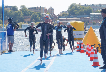 woman squirt: STOCKHOLM - AUG 22, 2015: Many female swimmer climbing up from the water in the Womens ITU World Triathlon series event August 22, 2015 in Stockholm, Sweden