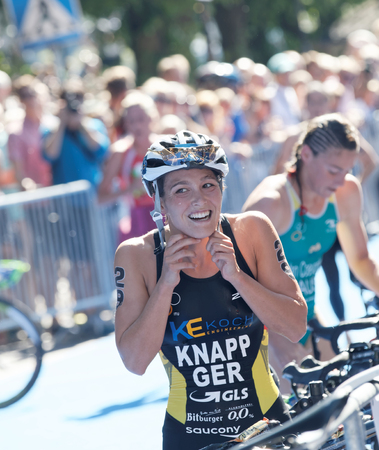 STOCKHOLM - AUG 22, 2015: Anja Knapp (GER) putting the helmet on in the transition zone from swimming to cycling in the Womens ITU World Triathlon series event August 22, 2015 in Stockholm, Sweden