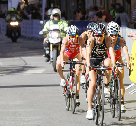 STOCKHOLM - AUG 22, 2015: Triathlete Yuko Takahashi  (JPN) cycling, followed by competitors in the Womens ITU World Triathlon series event August 22, 2015 in Stockholm, Sweden