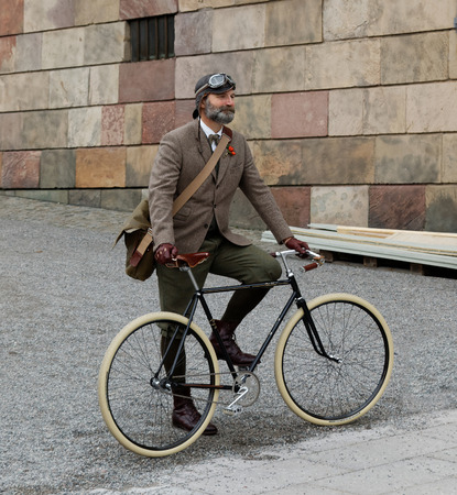 tweed: STOCKHOLM - SEPT 19, 2015: Man wearing old fashioned tweed clothes posing with a bicycle in the Bike in Tweed event September 19, 2015 in Stockholm, Sweden
