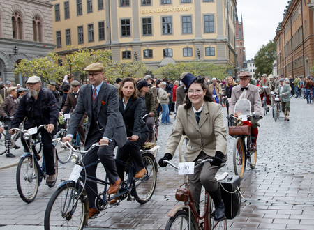 tweed: STOCKHOLM - SEPT 19, 2015: Group of cycling people wearing old fashioned tweed clothes in the Bike in Tweed event September 19, 2015 in Stockholm, Sweden