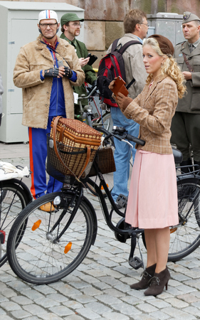 tweed: STOCKHOLM - SEPT 19, 2015: Blonde girl  in curly hair and group of people wearing old fashioned tweed clothes and bikes in the Bike in Tweed event September 19, 2015 in Stockholm, Sweden Editorial