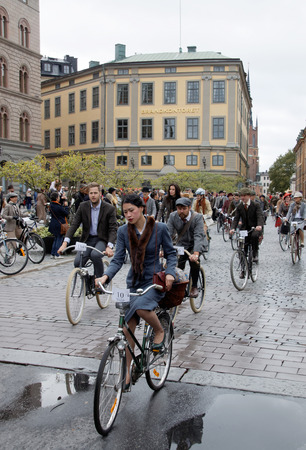 tweed: STOCKHOLM - SEPT 19, 2015: Group of elegant cycling people wearing old fashioned tweed clothes in the Bike in Tweed event September 19, 2015 in Stockholm, Sweden Editorial