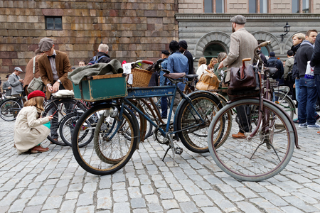 tweed: STOCKHOLM - SEPT 19, 2015: Group of elegant people with bicycles wearing old fashioned tweed clothes waiting for the start in the Bike in Tweed event September 19, 2015 in Stockholm, Sweden Editorial