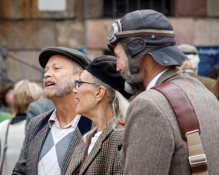 tweed: STOCKHOLM - SEPT 19, 2015: Elegant lady surrounded by two older men with beard wearing tweed in the Bike in Tweed event September 19, 2015 in Stockholm, Sweden Editorial