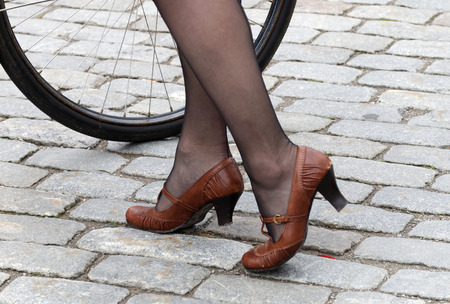 panty hose: Closeup of a womans legs in old fashioned leather shoes and panty hose with cycle wheel in the background