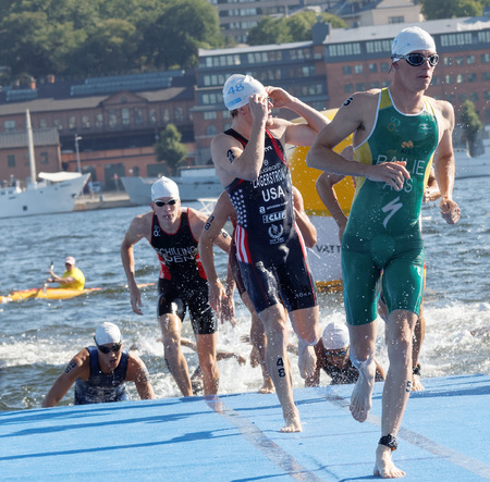 shilling: STOCKHOLM - AUG 22, 2015: Ryan Bailie, Eric Lagerstrom and other of male swimmers climbing up from the water in the Mens ITU World Triathlon series event August 22, 2015 in Stockholm, Sweden