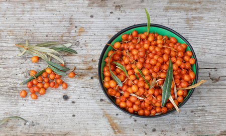 Sea buckthorn in a bowl and some laying on the side on a gray wooden plank