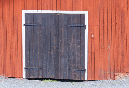 pepples: One black door with beautiful hinge in a red barn wall and white color around the door. Small pepples in front of the door