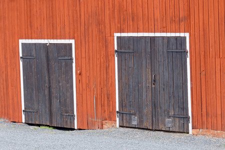 barn doors: Two black doors with beautiful hinge in a red barn wall and white color around the door. Small pepples in front of the doors