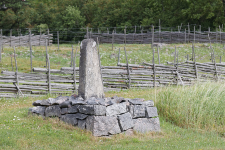 mile: Mile stone in the farm land telling the distance to the next village. Fences and trees in the background Stock Photo