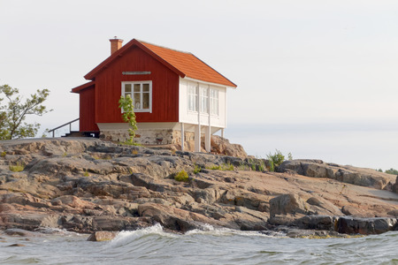 Red and white traditional cottage built on a rock in the archilelago