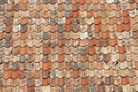 Roof made of aged roofing tiles in different shades of orange. The newly replaced tiles are darker and the older is covered with lichen