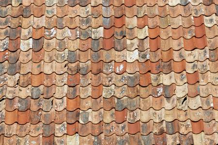 Techo de tejas envejecidas en diferentes tonos de naranja. Los azulejos recién reemplazados son más oscuros y los más viejos están cubiertos de líquenes. Foto de archivo